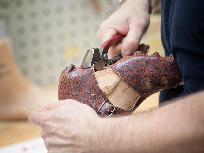 Mann arbeitet mit Zange an orthopädischem Schuh