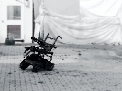 Verbrannter Rollstuhl steht auf geschmolzenen Rädern