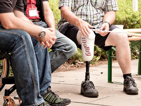 Rollstuhlfahrer, Fußgänger und Prothesenträger unterhalten sich