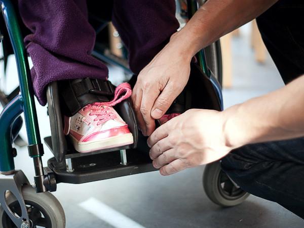 Pflegepersonal korrigiert Fußhaltung im Rollstuhl