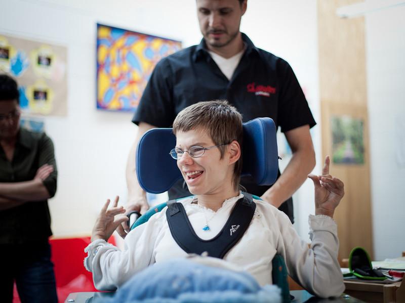 Mitarbeiter korrigiert Sitzposition bei jungem Mann im Rollstuhl