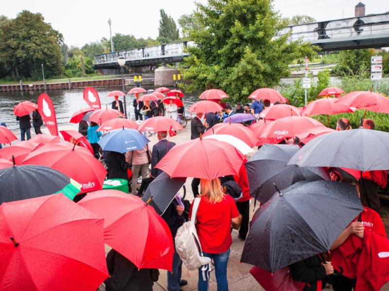 Viele Menschen unter vielen roten Regenschirmen.