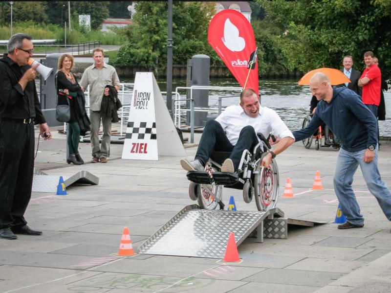 Ein Rollstuhlfahrer versucht ein künstliches Hinderniss zu überwinden.