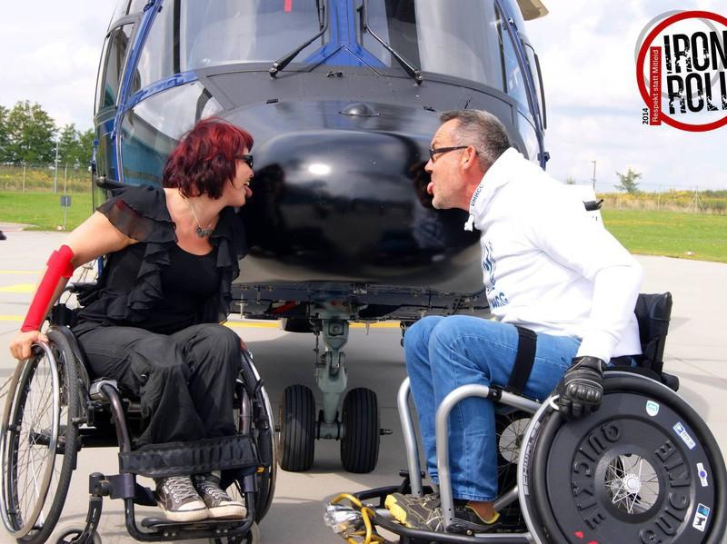 Zwei Rollstuhlfahrer strecken vor dem Bug eines Hubschrauber die Zungen raus.