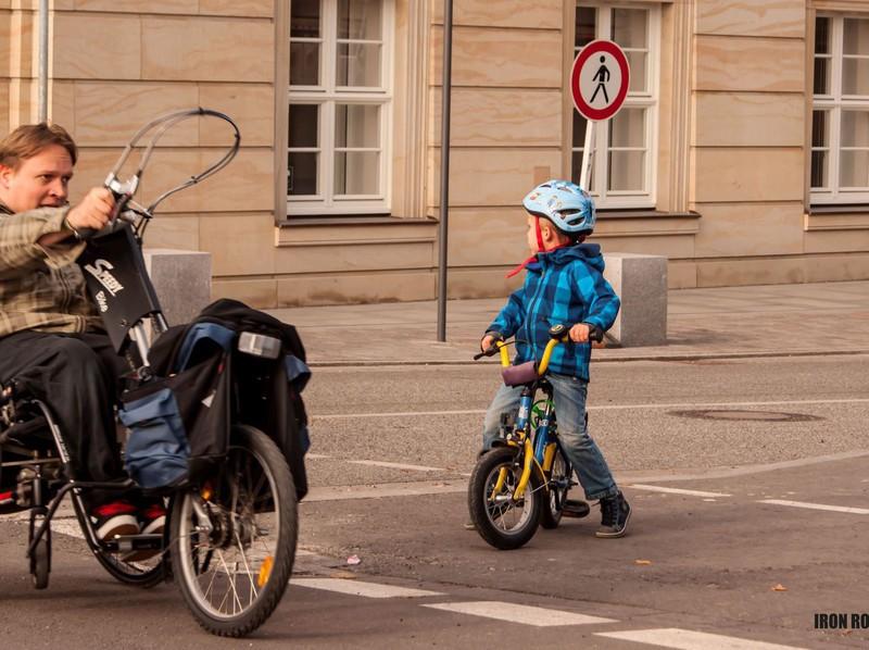 Kleines Kind auf einem Fahrrad gewährt Handbiker die Vorfahrt.