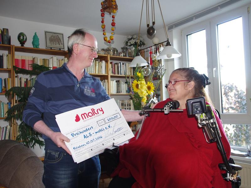 Scheckübergabe vom Maltry-Mitarbeiter an ALS-Betroffene.