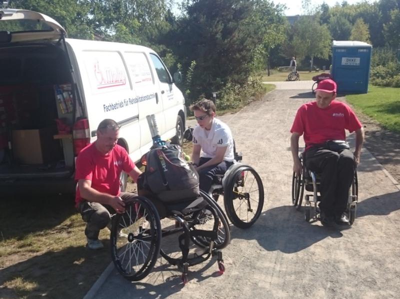 Mitarbeiter kniet vor Rollstuhl und repariert diesen.