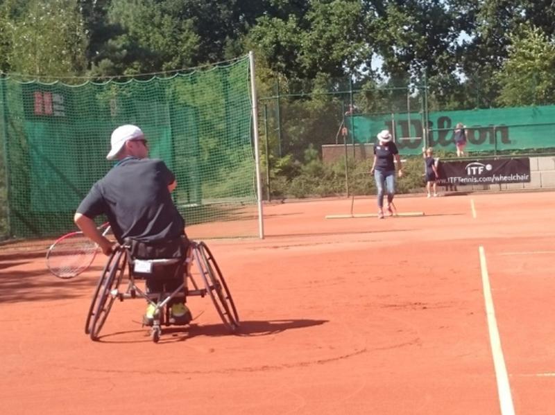 Athlet steuert mit Links seinen Rollstuhl und holt mit Rechts zur Rückhand aus.