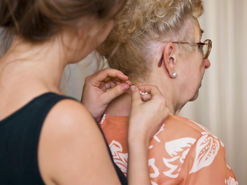 Junge Frau hilft Seniorin beim Anlegen von Schmuck